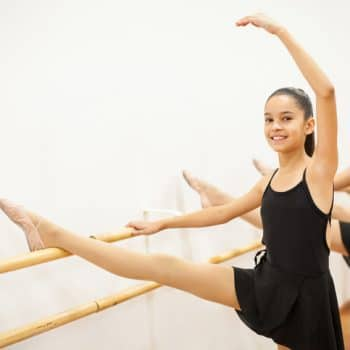 Portrait of a beautiful Hispanic girl practicing some ballet at a dance academy and smiling